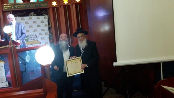 הרב בורשטיין מעניק תעודת הוקרה לרב אריאל