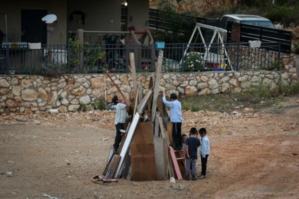 מדורות עד לגובה של מטר וחצי. ילדים מכינים קרשים למדורה