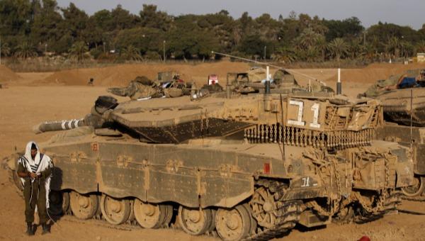 סרבנות או שיתוף פעולה? חייל מתפלל ליד טנק