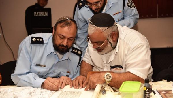 הרב רמי ברכיהו כותב אותיות בספר התורה שהוכנס לתחנת אשקלון