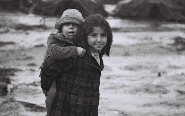 ילדה נושאת את אחיה במחנה העולים בית ליד
