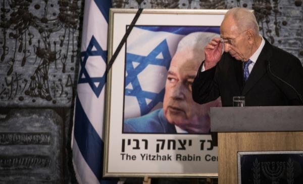 שמעון פרס ומאחוריו תמונה של יצחק רבין