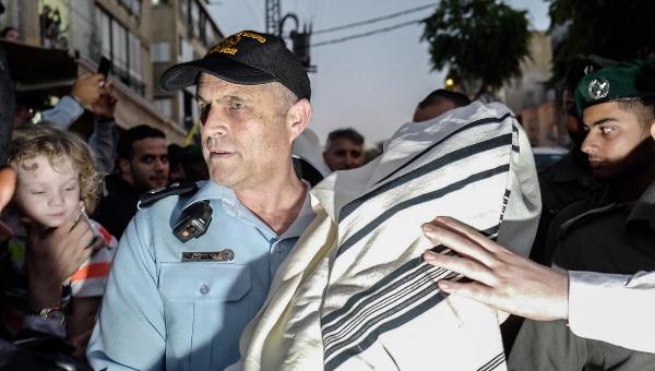קצין משטרה עם אחד מספרי התורה שנגנבו