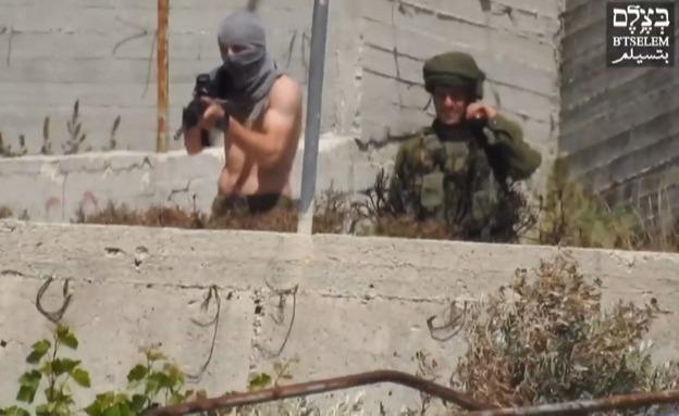 החייל רעול הפנים אוחז בנשק