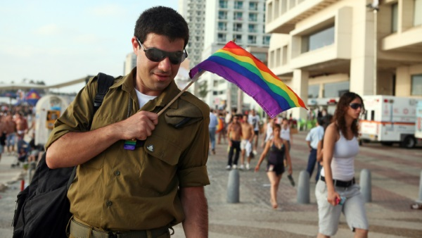 חייל עם דגל הקהילה הגאה. למצולם אין כל קשר לכתבה